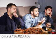 friends in suspense watching tv together at home. Стоковое фото, фотограф Яков Филимонов / Фотобанк Лори