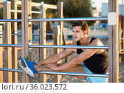 Strong man exercising in morning outdoors doing stretching workout on fitness station. Стоковое фото, фотограф Яков Филимонов / Фотобанк Лори