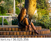 Teen girl outdoors in park is buckling her high-heeled sandals. Стоковое фото, фотограф Emil Pozar / age Fotostock / Фотобанк Лори