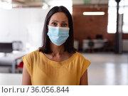 Portrait of caucasian businesswoman wearing face mask standing in office looking straight to camera. Стоковое фото, агентство Wavebreak Media / Фотобанк Лори