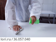 Midsection of cleaner wearing ppe suit disinfecting office workspace, wiping desks. Стоковое фото, агентство Wavebreak Media / Фотобанк Лори