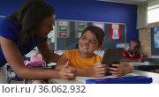 Diverse smiling female teacher helping schoolboy sitting in classroom, using tablet. Стоковое видео, агентство Wavebreak Media / Фотобанк Лори