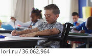 Portrait of happy mixed race schoolgirl sitting at classroom, making notes, looking at camera. Стоковое видео, агентство Wavebreak Media / Фотобанк Лори