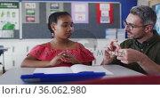 Diverse male teacher showing excersise to schoolgirl sitting at desk in classroom. Стоковое видео, агентство Wavebreak Media / Фотобанк Лори
