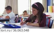 Portrait of caucasian schoolgirl sitting in classroom, making notes. Стоковое видео, агентство Wavebreak Media / Фотобанк Лори