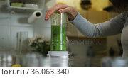 Caucasian woman preparing green vegetable smoothie in kitchen. Стоковое видео, агентство Wavebreak Media / Фотобанк Лори
