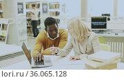 Female teacher working with african-american man in university library. Стоковое видео, видеограф Яков Филимонов / Фотобанк Лори