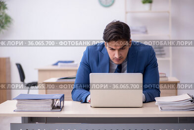 Young male employee sitting in the office