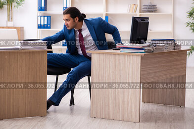 Young male employee in multitasking concept