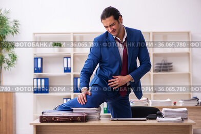 Young male employee doing sport exercises during break