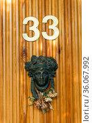 Closeup of metal door knocker made in the shape of a female head. Стоковое фото, фотограф Константин Лабунский / Фотобанк Лори