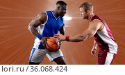 Two diverse male basketball players playing basketball against spot of light in background. Стоковое фото, агентство Wavebreak Media / Фотобанк Лори