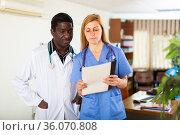 Experienced doctor reviewing medical history with female colleague. Стоковое фото, фотограф Яков Филимонов / Фотобанк Лори