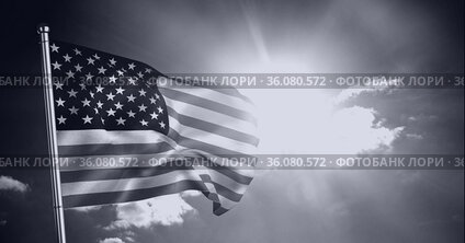 Monochrome composition of american flag on pole billowing against sunny, cloudy sky