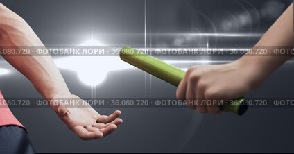 Mid section of hand passing a baton against spot of light on grey background