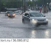 Автомобили едут по  глубоким лужам на проезжей части во время сильного ливня. Редакционное фото, фотограф Сайганов Александр / Фотобанк Лори