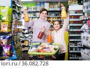 happy mother with daughter choosing refreshing beverages in supermarket. Стоковое фото, фотограф Яков Филимонов / Фотобанк Лори
