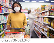 Woman in protective mask doing shopping in grocery department of supermarket. Стоковое фото, фотограф Яков Филимонов / Фотобанк Лори