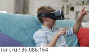 Happy caucasian boy at home, sitting on couch wearing vr headset and smiling. Стоковое видео, агентство Wavebreak Media / Фотобанк Лори