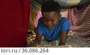 Happy african american boy using tablet and smiling lying in blanket camp. Стоковое видео, агентство Wavebreak Media / Фотобанк Лори