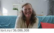 Portrait of happy senior caucasian woman sitting in living room smiling. Стоковое видео, агентство Wavebreak Media / Фотобанк Лори