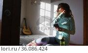 Happy mixed race woman preparing for workout, holding smartphone putting on earphones in sunny room. Стоковое видео, агентство Wavebreak Media / Фотобанк Лори