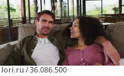 Happy diverse couple sitting on couch in living room, watching tv, embracing and talking. Стоковое видео, агентство Wavebreak Media / Фотобанк Лори