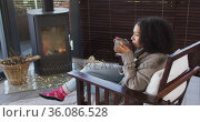 African american woman drinking coffee while sitting near the fireplace at vacation home. Стоковое видео, агентство Wavebreak Media / Фотобанк Лори