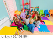 Young engaged teacher sitting with group of preschool children on... Стоковое фото, фотограф Zoonar.com/OKSANA SHUFRYCH / easy Fotostock / Фотобанк Лори