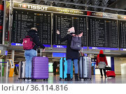 """""""Frankfurt am Main, Germany, travellers stand in front of the departure board in the terminal of the airport"""" Редакционное фото, агентство Caro Photoagency / Фотобанк Лори"""