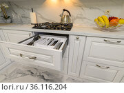 Open drawers with kitchenware at modern white kitchen. Стоковое фото, фотограф Сергей Старуш / Фотобанк Лори