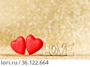 Two red handmade wooden hearts and word love on golden bright glitter... Стоковое фото, фотограф Zoonar.com/Ivan Mikhaylov / easy Fotostock / Фотобанк Лори