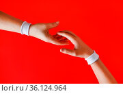 Give a helping hand. Hands with white bracelets reaching towards each... Стоковое фото, фотограф Zoonar.com/Alex Veresovich / easy Fotostock / Фотобанк Лори