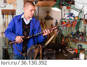 Gunsmith performing checkout of single-barrelled shotgun in weapons workshop. Стоковое фото, фотограф Яков Филимонов / Фотобанк Лори