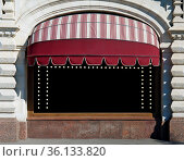 The restaurant window is decorated with a sun tent canopy and electric... Стоковое фото, фотограф Zoonar.com/Aleksandr Volkov / easy Fotostock / Фотобанк Лори