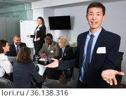 Successful business group with smiling Korean man foreground in. Стоковое фото, фотограф Яков Филимонов / Фотобанк Лори
