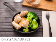 pieces of fried chicken breast with boiled broccoli egg in cast iron portioned skillet. Стоковое фото, фотограф Татьяна Яцевич / Фотобанк Лори