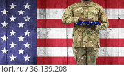 Composition of midsection of soldier with hand on folded american flag, against american flag. Стоковое фото, агентство Wavebreak Media / Фотобанк Лори