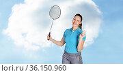 Portrait of caucasian female badminton player holding racket smiling against clouds in blue sky. Стоковое фото, агентство Wavebreak Media / Фотобанк Лори
