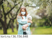 Little girl with dog wearing protective medical mask for prevent virus outdoors in the park. Стоковое фото, фотограф Дмитрий Травников / Фотобанк Лори