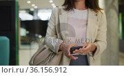 Caucasian businesswoman using smartphone in corridor of modern office. Стоковое видео, агентство Wavebreak Media / Фотобанк Лори