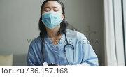 Portrait of happy asian female nurse wearing face mask holding tablet in hospital, smiling to camera. Стоковое видео, агентство Wavebreak Media / Фотобанк Лори