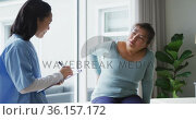 Asian female physiotherapist taking notes during consultation with female patient holding back. Стоковое видео, агентство Wavebreak Media / Фотобанк Лори