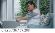 Asian woman using blood pressure monitor sitting on couch at home. Стоковое видео, агентство Wavebreak Media / Фотобанк Лори