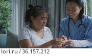 Smiling asian female doctor talking to happy female patient about her medication at hospital. Стоковое видео, агентство Wavebreak Media / Фотобанк Лори