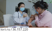 Asian female nurse wearing face mask giving covid vaccination to female patient in hospital. Стоковое видео, агентство Wavebreak Media / Фотобанк Лори