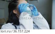 Asian female nurse wearing face mask putting on protective safety glasses in hospital. Стоковое видео, агентство Wavebreak Media / Фотобанк Лори