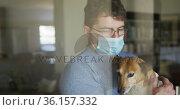 Caucasian man wearing face mask, standing at window and petting dog. Стоковое видео, агентство Wavebreak Media / Фотобанк Лори