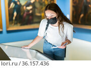 Young girl in a protective mask in the museum looks at the exposition behind a glass case. Стоковое фото, фотограф Яков Филимонов / Фотобанк Лори