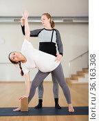 Pregnant woman practices yoga with an instructor. Revolved side angle pose or Parivrtta Parsvakonasana. Стоковое фото, фотограф Татьяна Яцевич / Фотобанк Лори